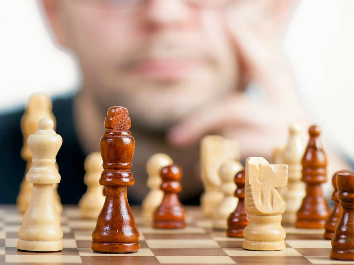 chess player strategizing looking at chess board